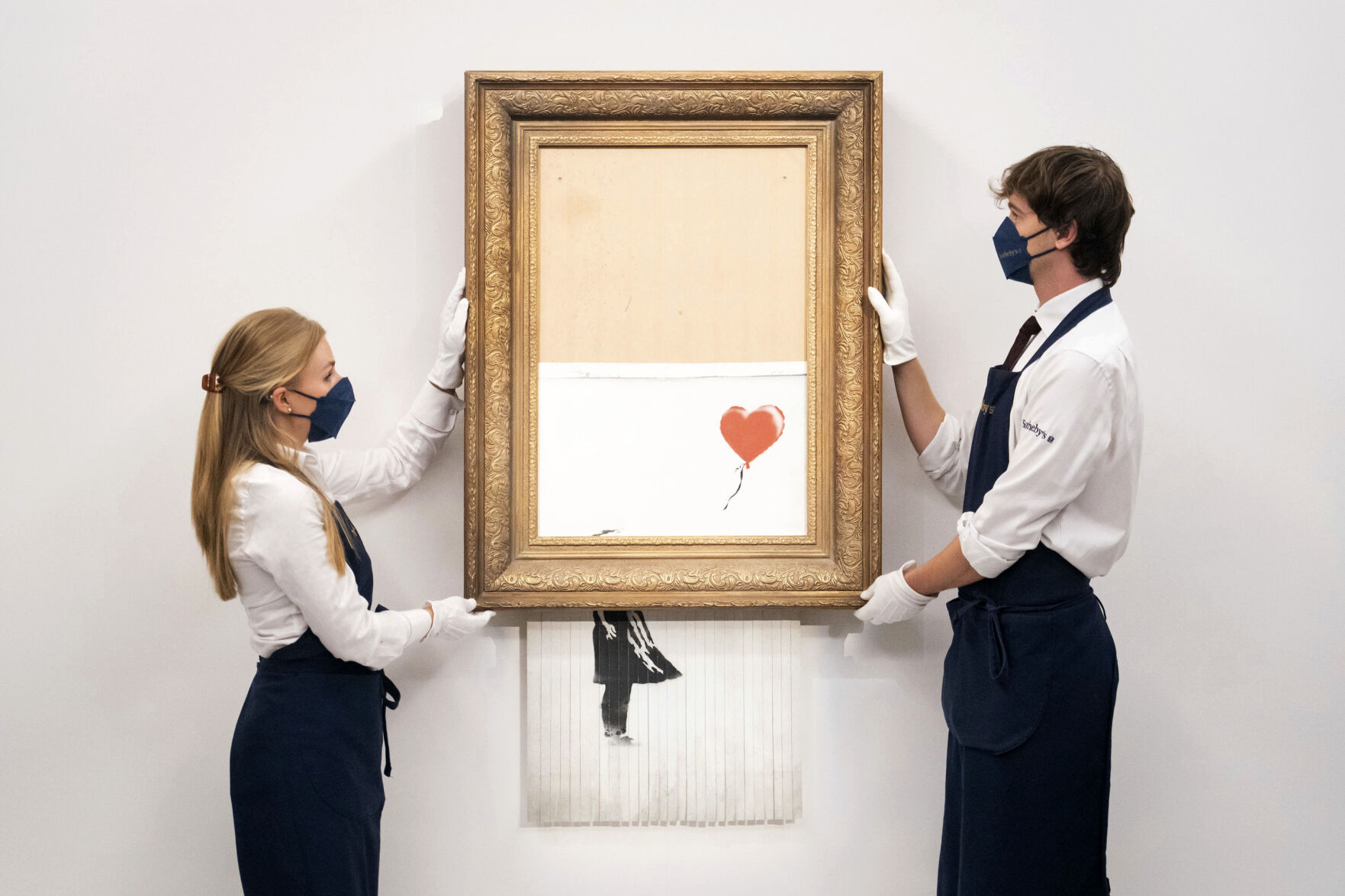 """<p>FILE - In this Sept. 3, 2021 file photo, art handlers at Sotheby's auction house hold Banksy's 'Love is in the Bin', before it returns to auction at Sotheby's, London, The work by British street artist Banksy that sensationally self-shredded just after it sold for .4 million could make several times that price at an auction on Thursday, Oct. 14, 2021. """"Love is in the Bin"""" is being offered by Sotheby's in London, with a pre-sale estimate of 4 million pounds to 6 million pounds (.5 million to .2 million). (Dominic Lipinski/PA via AP, file)</p>"""