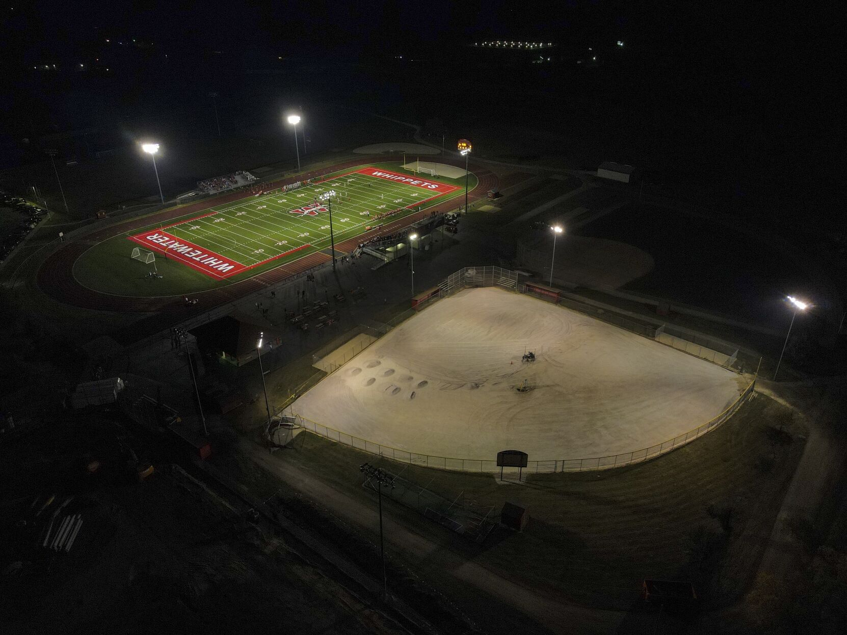 <p>A football field, top, and baseball field under construction are lit up at Whitewater High School Friday, Oct. 1, 2021, in Whitewater, Wis.</p>